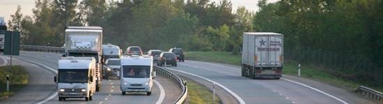 Bilar och lastbilar på större väg.