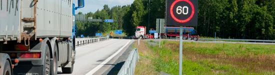 Lastbil på väg närmar sig digitalt vägmärke som visar 60 km/tim