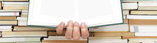 hand som håller en bok i hög med andra böcker