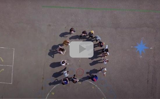 Skolbarn står i en cirkel på en skolgård, sett från drönarperspektiv