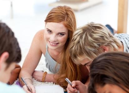 Bild på fyra ungdomar, en rödhårig tjej tittar upp och ler mot kameran. Foto: Wavebreakmedia