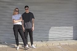 Bild på två ungdomar med solglasögon som står med en vägg som bakgrund. Foto: ArtesiaWells