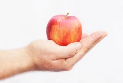 Bild på en utsträckt hand med ett rött äpple Foto: Eva Soderberg
