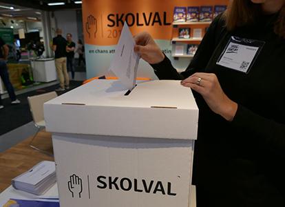Bild från Skolval 2018/2019 där en person lägger ner valkuvert i röstlåda.