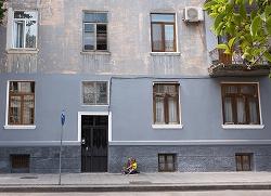 Bild på husfasad och två barn som sitter på trottoaren framför huset. Foto: Shablovskyistock