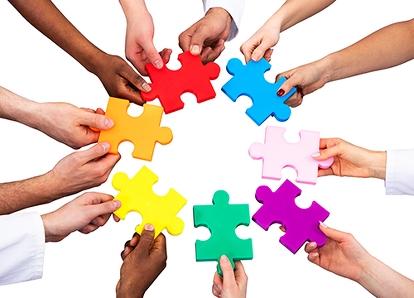 12 händer håller i 7 pusselbitar i olika färger. Tillsammans formar de en cirkel.