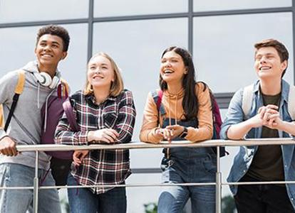 Bild på fyra ungdomar som står och lutar sig mot ett räcke och skrattar. Foto: LightField