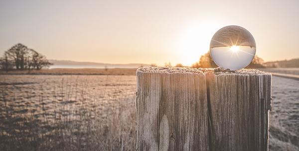 Bild på vinterlandskap där solen speglas genom glaskula. Foto: Kasper Nymann