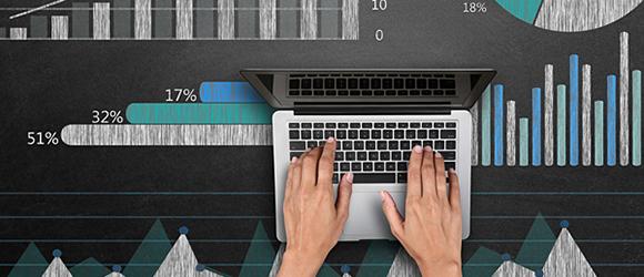 Temabild med händer som skriver på en dator, mot en bakgrund med grafer