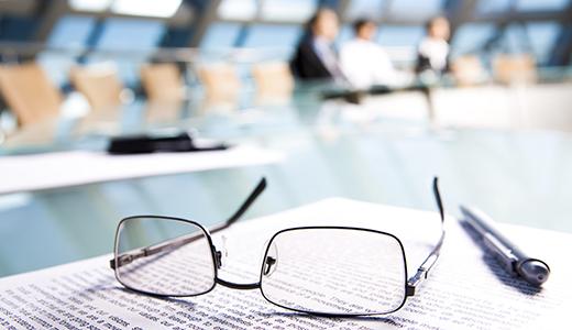 Temabild med papper, glasögon och penna i förgrunden mot bakgrund av personer vid ett bord