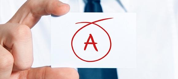 Hand som håller i en lapp med ett A