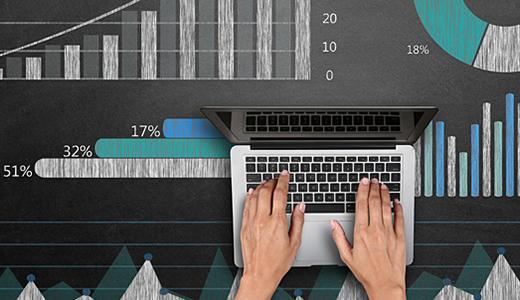 Temabild med händer som skriver på en bärbar dator mot bakgrund av diagram.