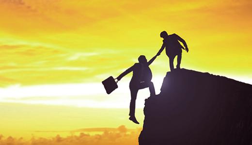 En person som hjälper en annan upp på en bergstopp.