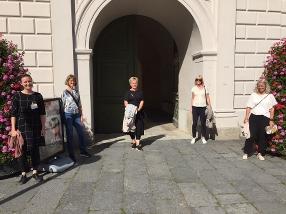 De fem personerna från projektgruppen står utomhus framför en port med gott om avstånd mellan sig.