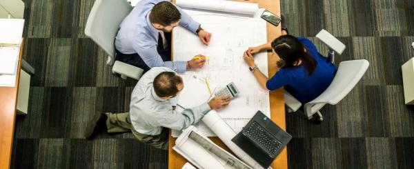 Tre personer sitter vid ett bord och samtalar med papper, dator och kalkylator framför sig.