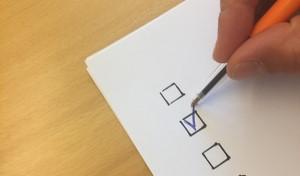 Närbild på en penna som skriver i en bock i en ruta.