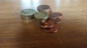 En hög med mynt ligger på ett bord.