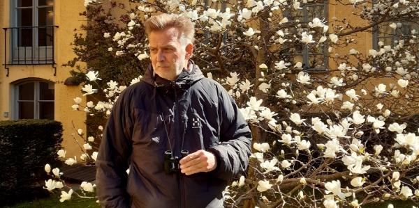 Man med kikare står framför blommande magnoliaträd.