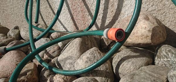 En grön vattenslang är ihoprullad och hänger på en stenvägg.