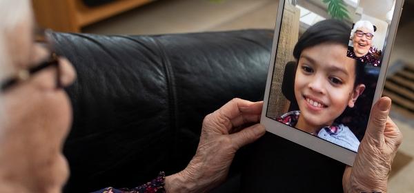 Kvinna pratar med sitt barnbarn via en läsplatta