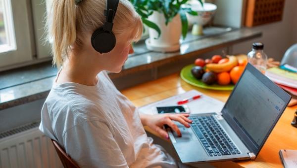 En tjej med hörlurar framför en dator.
