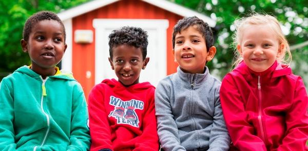 Barn framför en röd stuga