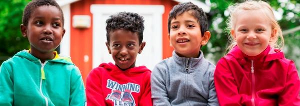 Fyra barn sitter framför en liten röd stuga