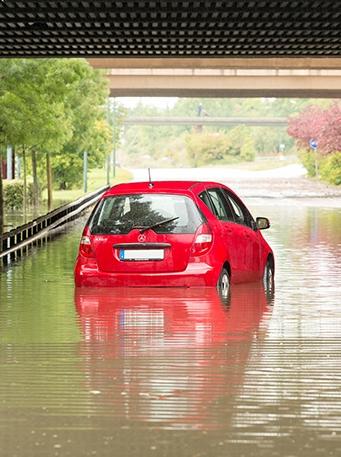Bil som kör där det är översvämmat av regn.
