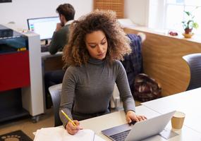 En ung kvinna sitter framför en dator och antecknar i ett block.