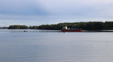 Sanering av kvicksilver i Notviken utanför Luleå. Spegelblank sjö med båt och skog i bakgrunden. Foto: Jennifer Lundbäck.
