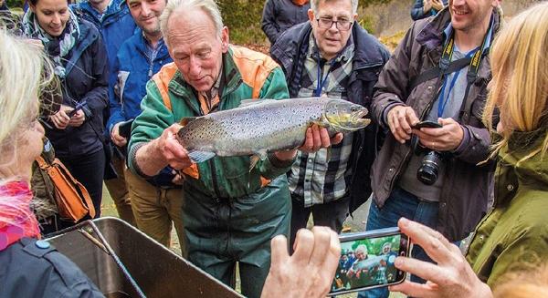 En grupp personer står och tittar på en fisk. Foto: Peter Nolbrant.