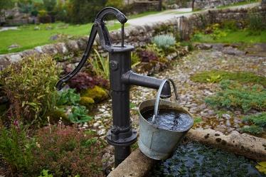 Brunn med pump. Spann. Foto: Pixabay.