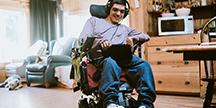 En person i rullstol som använder en surfplatta. Foto