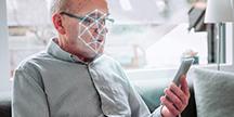 En person som använder en smartphone och ansiktsigenkänning. Foto/Illustration