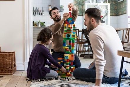 Två vuxna män bygger ett legotorn tillsammans med ett barn.